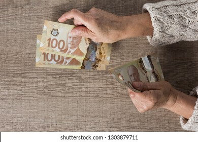 Money from Canada: Canadian Dollars. Overhead of senior person holding bills.
