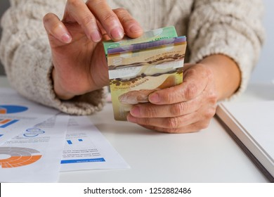 Money from Canada. Dollars. Canadian currency. Person handling papernotes on desk.