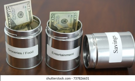 Money in cans for budgeting food, entertainment, and savings. Savings can is empty.