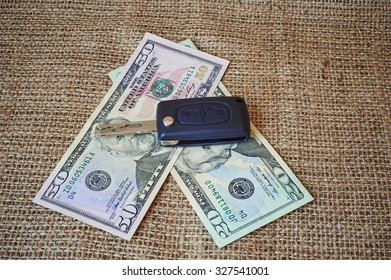 Money and car keys on a burlap background.