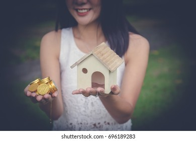 money cash and a model home in woman hand. Young lady hands holding Little house toy and golden coins. property mortgage, real estate loan, sell owner value concept. young buyer saving money for home.