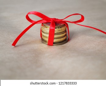 Money as christmas gift, coins on a table with red bow