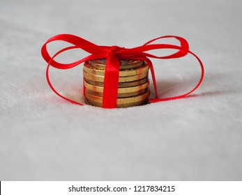 Money as christmas gift, coins on a white background with red bow