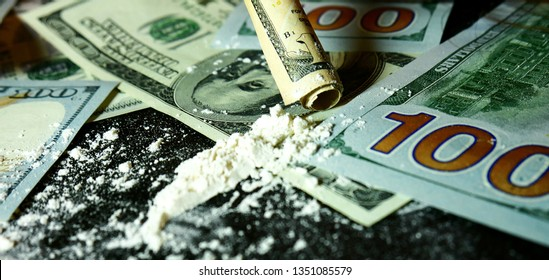 money and cocaine. Addiction. Drug use.  Hundred-dollar bills, white powder (like cocaine) on the black table close-up. Illegal drugs and dirty money. A lot cocaine.
