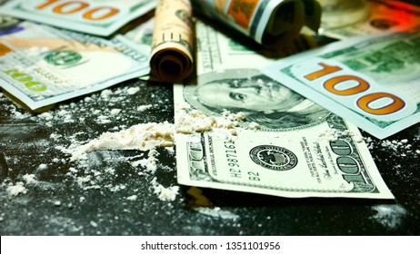 Money and cocaine. Addiction. Drug use. Hundred-dollar bills, white powder (like cocaine) on the black table close-up. Drug dealer. Illegal drugs and dirty money. A lot cocaine.