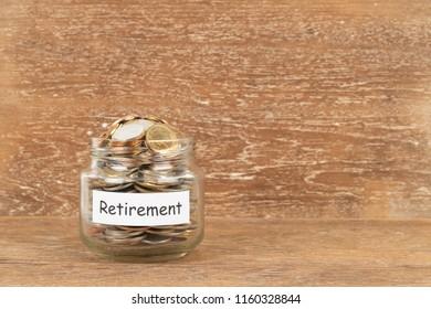 Money coin jar on wooden background retirement saving concept