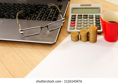 Money coin stack and calculator and eyeglasses for business and finance concept