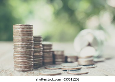 Money coin stack step growth with blurred background jar and green leaf, Save money and investment concept, Copy space