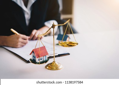Money coin with wooden house on gold brass balance scale. Saving money for real estate with buying a new home and loan for prepare in the future concept.