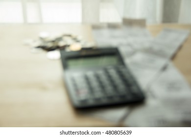 money coins, bills under calculator on wood table, natural day light, selective focus, space for copy, motion blurred