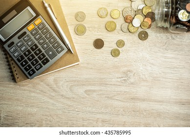 Money (coins), calculator and some stationery on wood table, top view with copy space - financial background concept