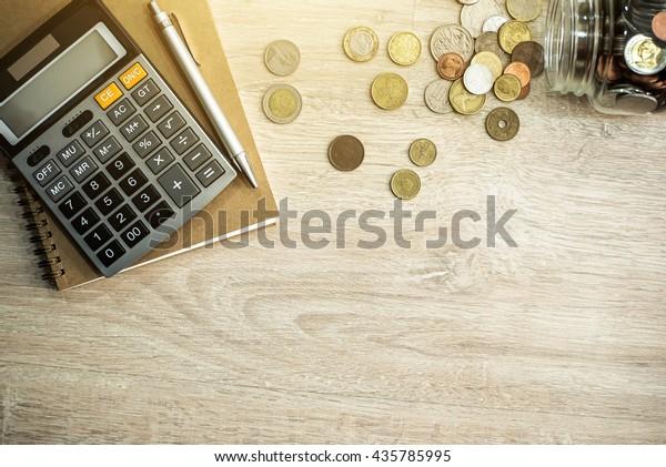 Geld (Münzen), Taschenrechner und einige Schreibwaren auf Holztisch, Draufsicht mit Kopienraum - Finanzhintergrund