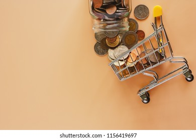 Money and coins form glass jar to mini shopping cart or trolley on beige color background for spending plan, investment, business and finance concept