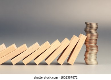 Money coins heap still balance and stop the falling domino, financial stability concept