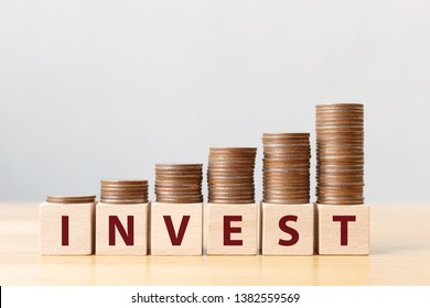 Money coins stack stair as step growing growth and wooden cube block with word INVEST. Investment and save money concept