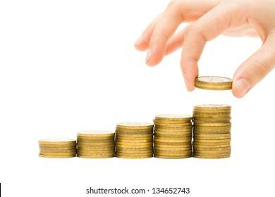 Money concept - hand putting coins on golden money stacks