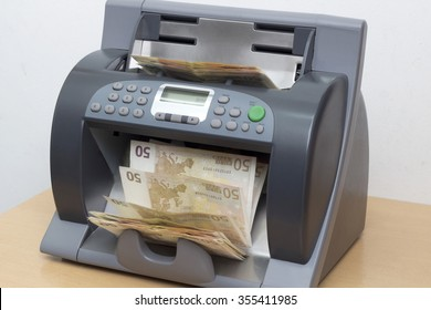 Money in the counting Machine on the Desk