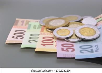México Money, Currency of México, Pesos, various bills and coins, close-up on dark background. Cash money