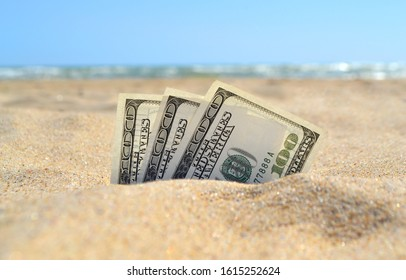 Money dolars half covered with sand lie on sandy beach near sea ocean waves on sunny summer day close-up. Money grows out of the ground. Concept finance money holiday relax vacation. - Shutterstock ID 1615252624