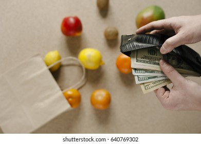money dollars. package of fruit and wallet with cash. The pricing of goods. poverty. action. gift. In the supermarket and buy products and fruits and vegetables.