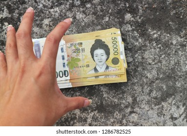 Money dropped on dirty floor, hand