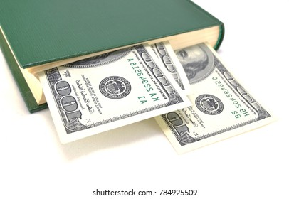 Money embedded in a book on a white background close-up