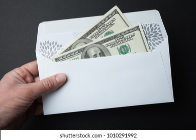 Money in an envelope on a black background. 100 dollar bills.