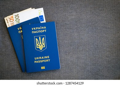 Money euro and two Ukrainian blue passports on a gray cloth herringbone background.