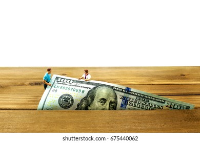 Money falls through a crack on a brown floor with partial white background. Monetary concept to encourage people to seek money management solutions.