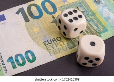 Money, finance and gambling concept: Close up on an European 100 (hundred) EUR, Euro banknote. Two white dice on top showing the numbers 1 and 6