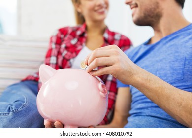 money, finance, investment, saving and people concept - close up of happy couple putting euro coin to piggybank
