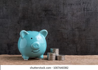 Money or finance saving concept, blue piggy bank with stack of coins beside on wood table and black cement wall with copy space, compound interest in investment or savings account awareness.