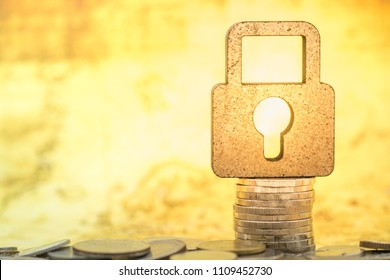 Money, finance and security concept. Close up of wooden cutting as master key lock  icon on stack of coins with pile of coin with world map as background.