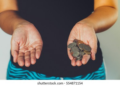 money and finances concept - close up of Asian womans in black t-shirt hands putting coins