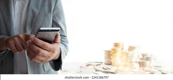 Money, Financial, Business Growth concept, BBusiness man using smart phone for checking mobile banking app. Stock shart and pie of coins background. Close up of hond on mobile.