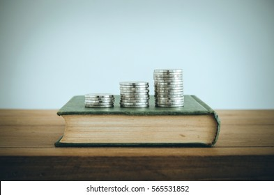 Money, Financial, Business Growth concept, Coin stacks on old book. Vintage filter.