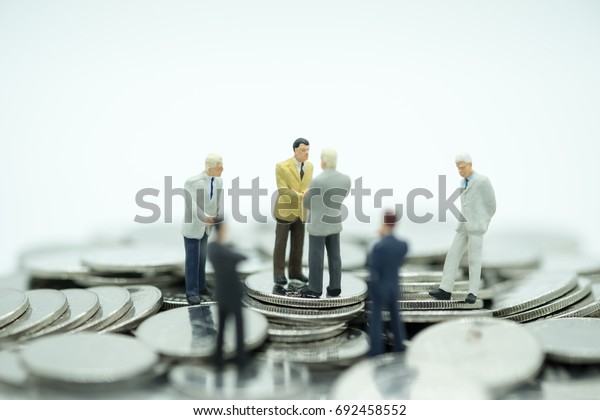 Money, Financial, Business Growth concept, Group of businessman miniature people figures standing, meeting and hand shake  on pile of coins