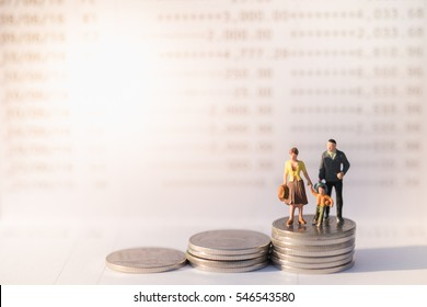 Money, Financial, Business Growth and family  concept, Miniature figures businessman, woman and child stand on top of stack of coins in front of book bank under morning sun light