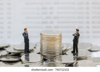 Money, Financial, Business planning and Growth concept, Two Businessman miniature figures stand on pile of coins and looking and thinking to stack of coins with bank passbook as background.