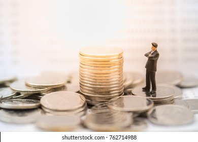 Money, Financial, Business planning and Growth concept, Businessman miniature figure stand on pile of coins and looking and thinking to stack of coins with bank passbook as background.