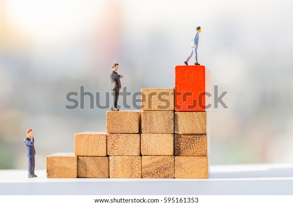 Money and financial concepts. Miniature people: Small figure standing on wooden block stairway.