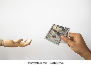 Money Financial and Payment Concept. Closeup of woman hand holding and give a 100 US Dollar bank note to wooden hand model.