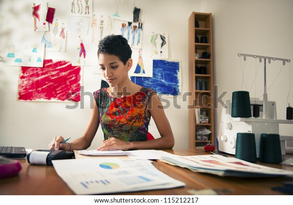 Money and financial planning, young hispanic self-employed woman checking bills and doing budget with calculator, computer and papers in fashion design studio