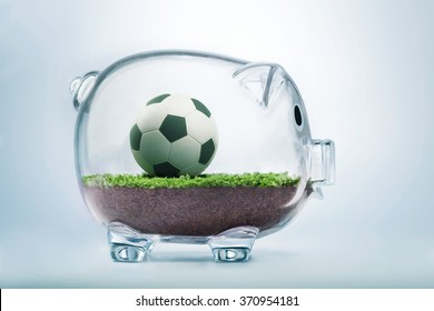 Money and football business concept with soccer ball inside transparent piggy bank