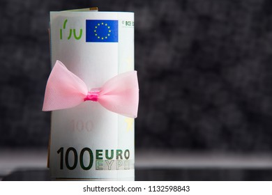 Money as a gift. Euro bills with pink bow close-up on black background.