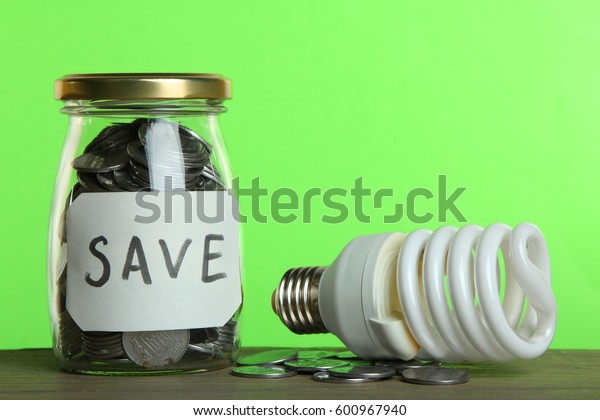 Money in a glass jar and a light bulb on a wooden table on a green background