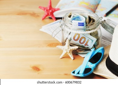 Money in glass jar on wooden table. Savings for summer holidays, vacation, travel and trip. Empty space for text