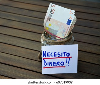Money in glass jar and the Spanish words necesito dinero on a white note