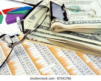 Money, glasses and pen on the table with financial data