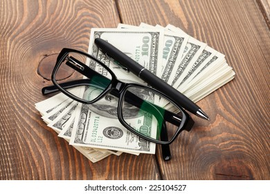 Money, glasses and pen on wooden table